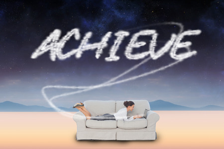 The word achieve and business woman lying on couch against serene landscape photo