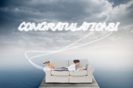 The word congratulations! and business woman lying on couch against cloudy sky over ocean photo