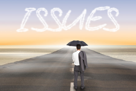 The word issues and businessman standing back to camera holding umbrella and jacket on shoulder against road leading out to the horizon photo