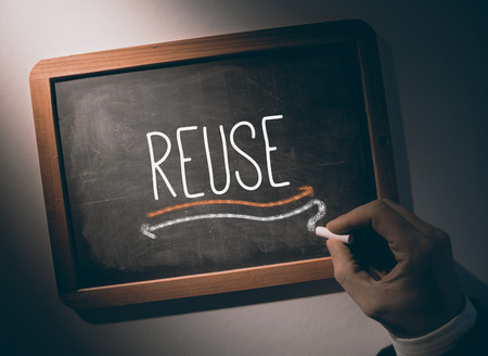 Hand writing the word reuse on black chalkboard photo