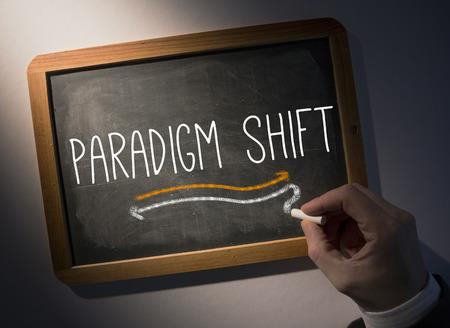 paradigm: Hand writing the word paradigm shift on black chalkboard