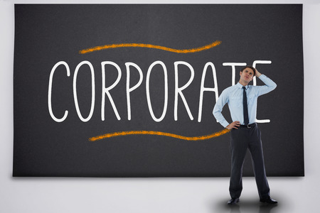 Businessman thinking against the word corporate photo