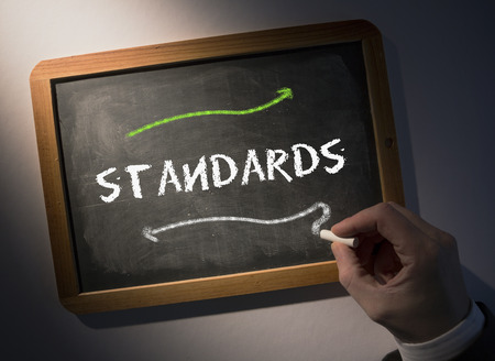 Hand writing the word standards on black chalkboard