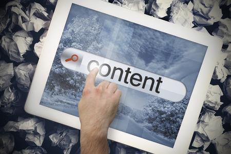 Hand touching the word content on search bar on tablet screen on crumpled papers photo