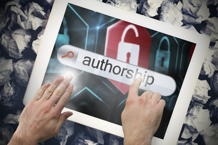 authorship: Hand touching the word authorship on search bar on tablet screen on crumpled papers Stock Photo