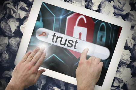 Hand touching the word trust on search bar on tablet screen on crumpled papers photo