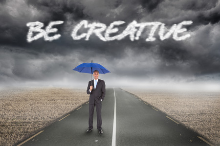 be dressed in: The word be creative and businessman smiling at camera and holding blue umbrella against misty brown landscape with street Stock Photo
