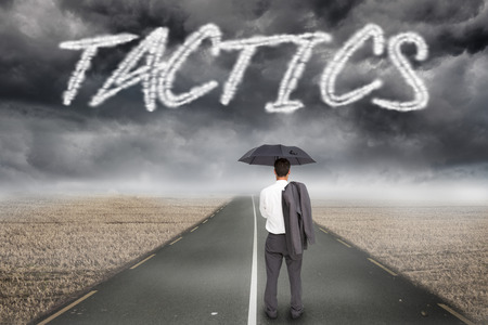 The word tactics and businessman standing back to camera holding umbrella and jacket on shoulder against misty brown landscape with street photo