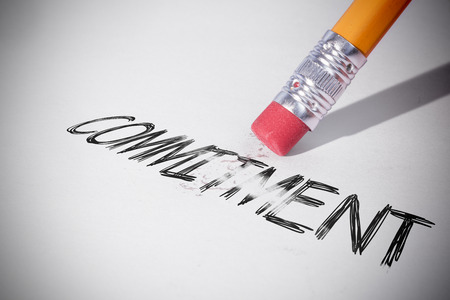 erasing: Pencil erasing the word commitment on paper Stock Photo