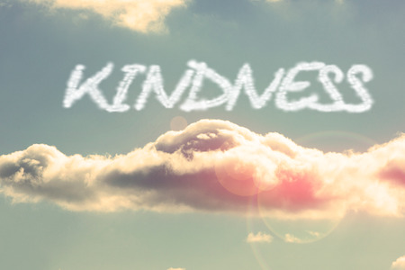 kindness: The word kindness against bright blue sky with cloud