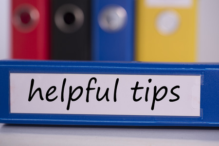 The word helpful tips on blue business binder photo