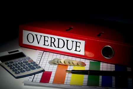 overdue: The word overdue on red business binder on a desk