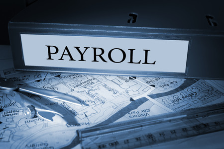 payroll: The word payroll on blue business binder on a desk