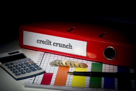 The word credit crunch on red business binder on a desk