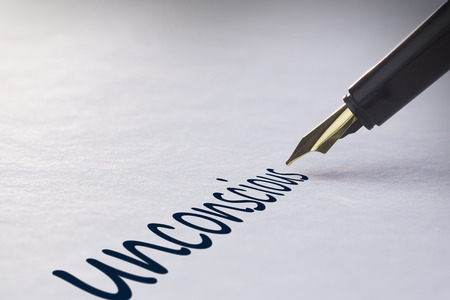 knocked out: Fountain pen writing the word unconscious Stock Photo