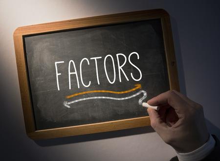 factors: Hand writing the word factors on black chalkboard