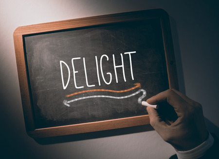 Hand writing the word delight on black chalkboard Stock Photo