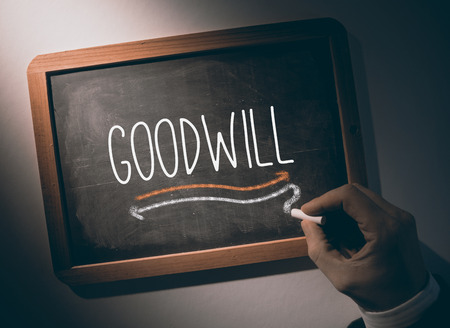 goodwill: Hand writing the word goodwill on black chalkboard
