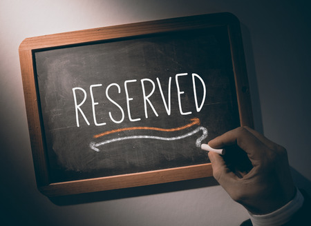 booked: Hand writing the word reserved on black chalkboard