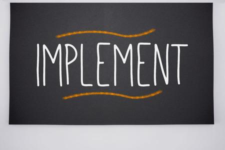The word implement written on big blackboard Stock Photo