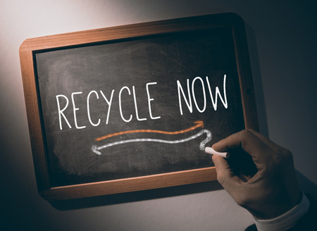 Hand writing the word recycle now on black chalkboard photo
