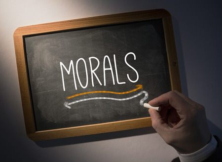 morals: Hand writing the word morals on black chalkboard