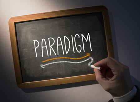 paradigm: Hand writing the word paradigm on black chalkboard Stock Photo