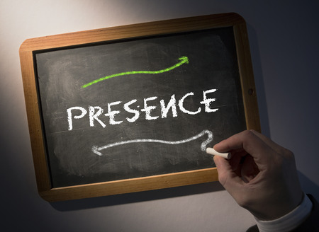 presence: Hand writing the word presence on black chalkboard Stock Photo