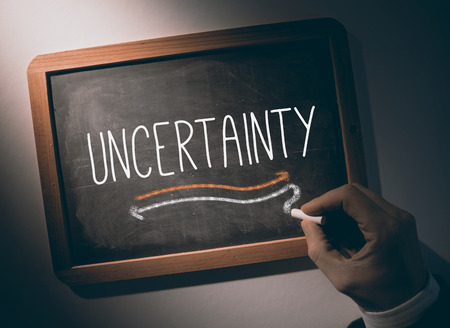 unknowing: Hand writing the word uncertainty on black chalkboard