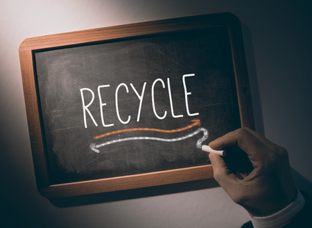 Hand writing the word recycle on black chalkboard photo