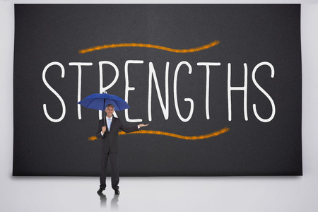Businessman holding umbrella against the word strengths