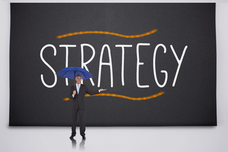 Businessman holding umbrella against the word strategy photo