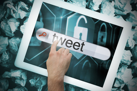 Hand touching the word tweet on search bar on tablet screen on crumpled papers Stock Photo - 26807185