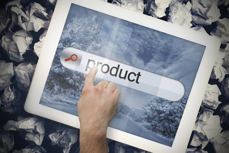 Hand touching the word product on search bar on tablet screen on crumpled papers photo