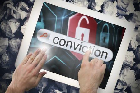 conviction: Hand touching the word conviction on search bar on tablet screen on crumpled papers Stock Photo