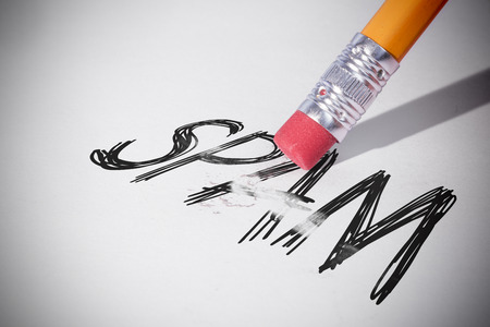 unsolicited: Pencil erasing the word spam on paper Stock Photo