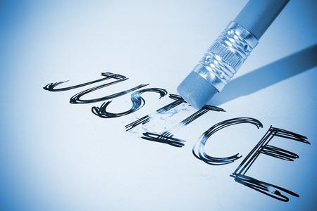 erasing: Pencil erasing the word justice on paper