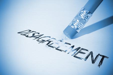 erasing: Pencil erasing the word disagreement on paper Stock Photo