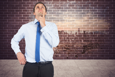 Thinking businessman touching his chin against splash on wall revealing cityscape photo