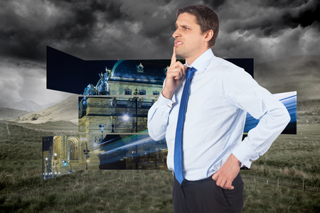 Thinking businessman touching his chin against stormy countryside background photo