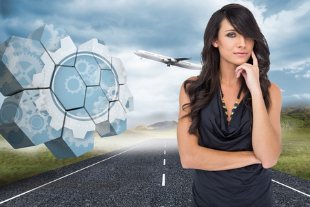Pensive elegant dark haired model posing with finger on her cheek against 3d plane taking off over street photo