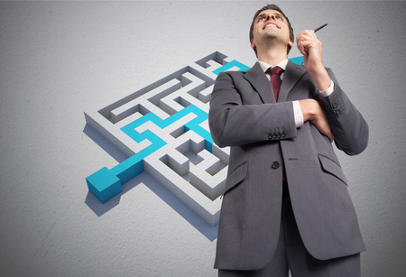 Thoughtful businessman holding pen against blue arrow solving puzzle photo