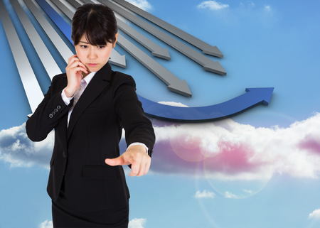 curved arrows: Thoughtful businesswoman pointing against blue and grey curved arrows pointing against sky