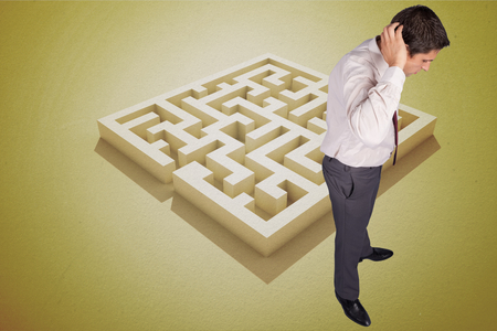 Thinking businessman scratching head against yellow puzzle photo
