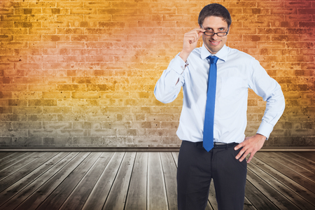 Thinking businessman tilting glasses against room with brick wall photo