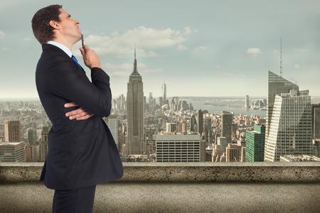business skeptical: Negocios de pensamiento que sostiene la pluma contra el balc�n con vistas a la ciudad