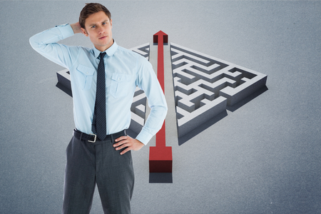 Thoughtful businessman with hand on head against red arrow cutting through puzzle photo