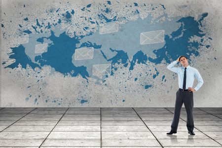 Thoughtful businessman with hand on head against splash showing global communications photo