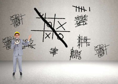 Architect with hard hat shouting with a megaphone against tic tac toe photo