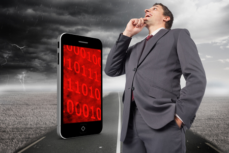 Thoughtful businessman with hand on chin against stormy landscape with street photo